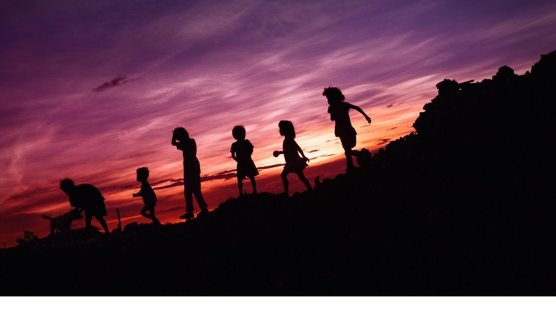 Kids playing at sunset.