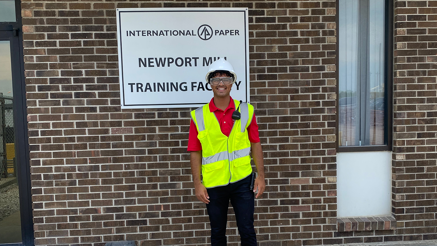 Kelvin Borges stands in front of International Paper sign