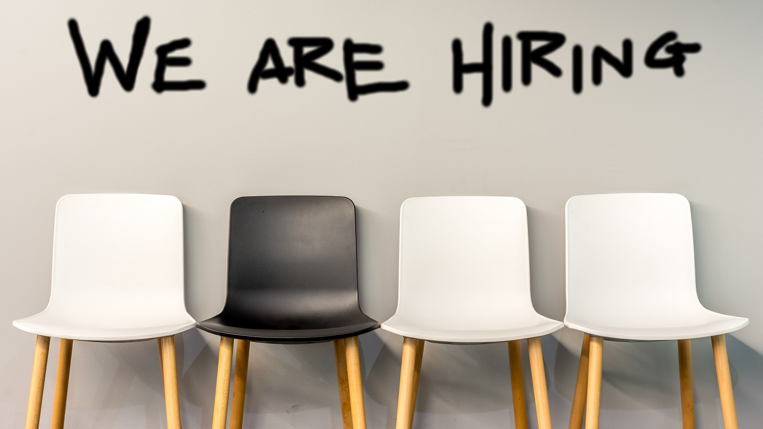 """Sign """"We Are Hiring"""" over Three Chairs and One Black Chair"""