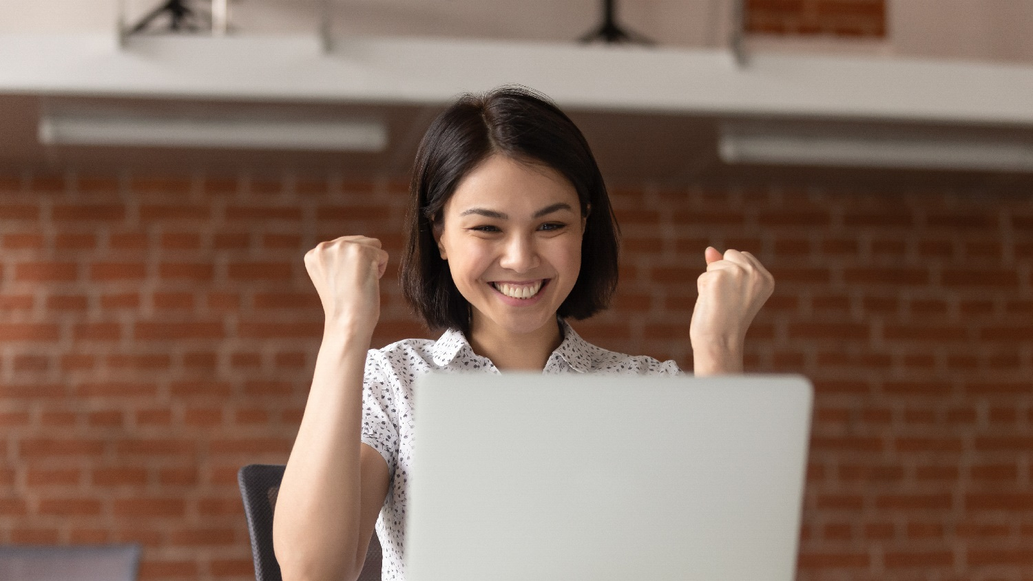 Young Woman Looking Happily at Her Laptop