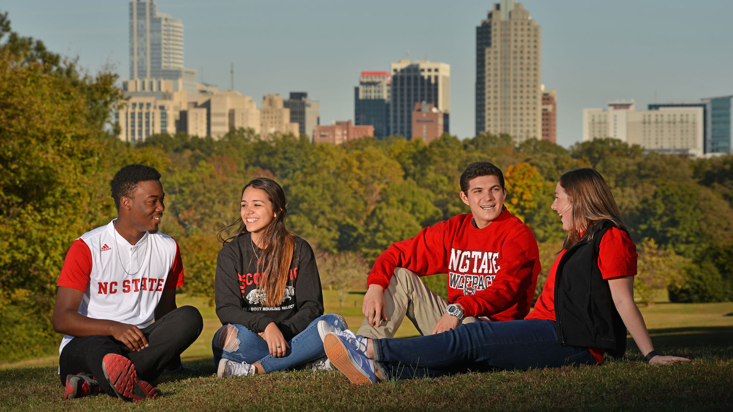 Students Sitting on the Lawn in front of Raleigh Skyline - Visit Us - College of Natural Resources NCState University